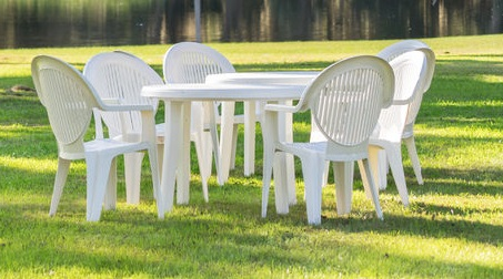 36305411 - white plastic table and chairs outside in a garden on green lawn by a pond or lake in the afternoon sun and a peaceful relaxing serene tranquil setting